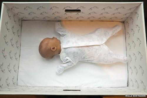 Bebe a dormir numa caixa de papelão