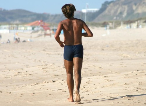 homem jeitoso a correr na praia