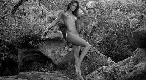 Foto a preto e branco, mulher nua no bosque, calendário pirelli.