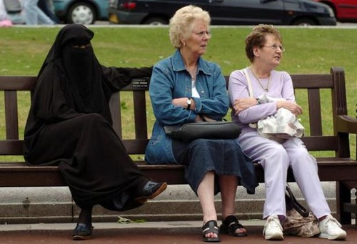 Three women share a bench in Glasgow during a vigi