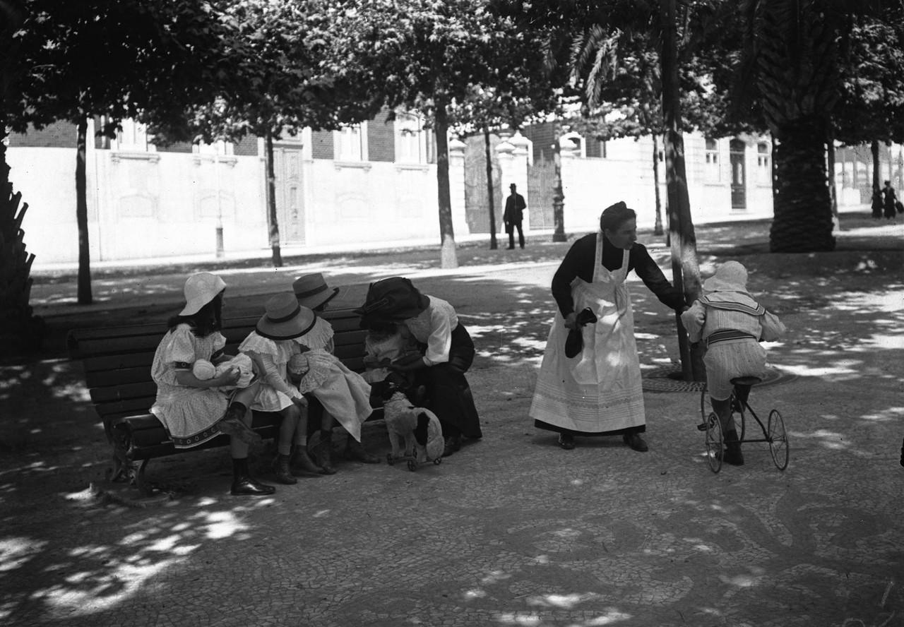 Ama com crianças num banco de jardim da avenida d